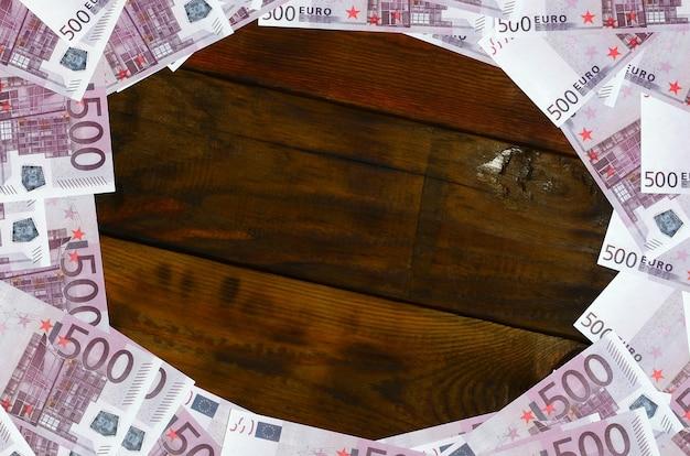 Множество фиолетовых купюр стоимостью 500 евро лежат на деревянной поверхности с пустым блокнотом в центре изображения.