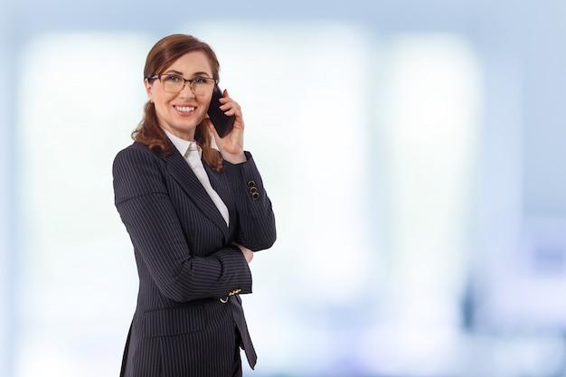 Портрет красивой коммерсантки 50 ушей старых с мобильным телефоном в офисе.