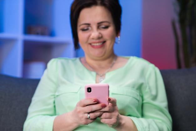 電話を使用して成熟した女性の手。高齢者の手の中のスマートフォン。スマートフォンのソーシャルネットワークで50代女性のテキストメッセージ