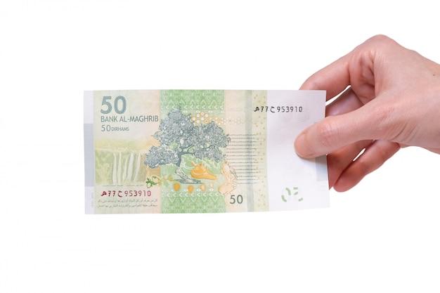 Женщина, держащая 50 марокканских дирхамских банкнот в руке на белом