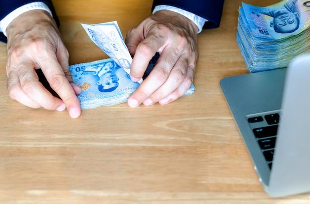 男の手が新しいタイのお金50バーツ紙幣を数えます。