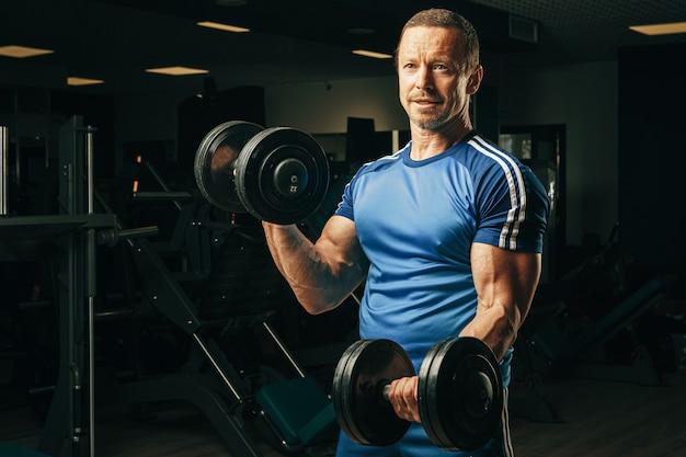 ジムでウェイトトレーニングをしている彼の50代のシニア男性