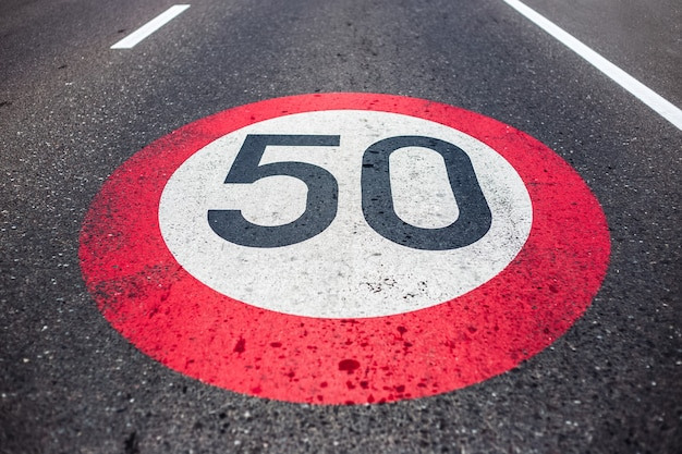 아스팔트 도로에 50km / h 속도 제한 표지판이 그려져 있습니다.