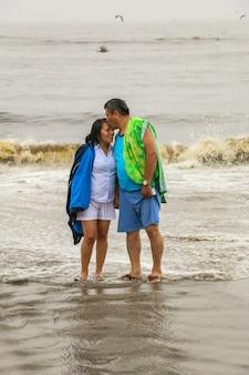 50세의 성숙한 남녀가 행복하고 사랑에 빠진 해변을 걷는다