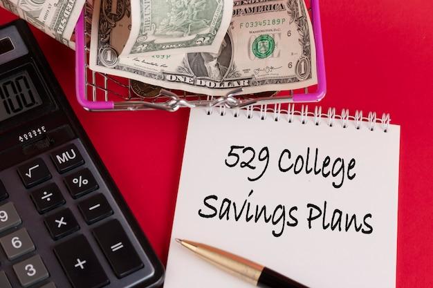 529 college savings plans, 법률 텍스트는 계산기와 빨간색 배경이 있는 흰색 메모장에 작성됩니다.