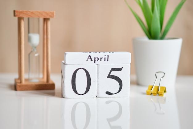 Дата на белых деревянных кубиках - пятая, 5 апреля на белом столе.