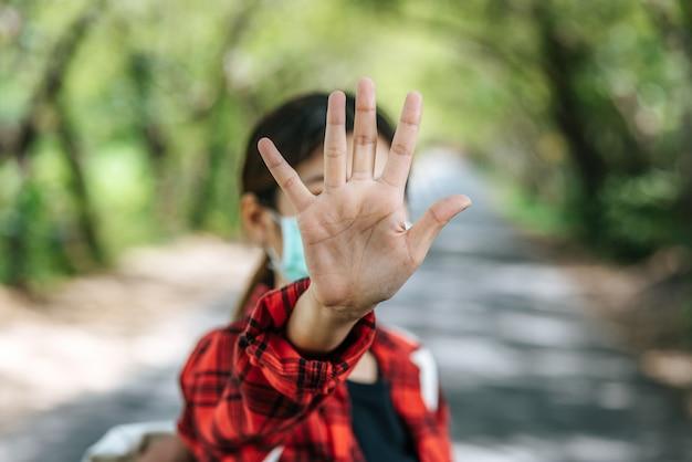 バックパックを背負って5本の指を上げて路上禁止をする女性観光客。