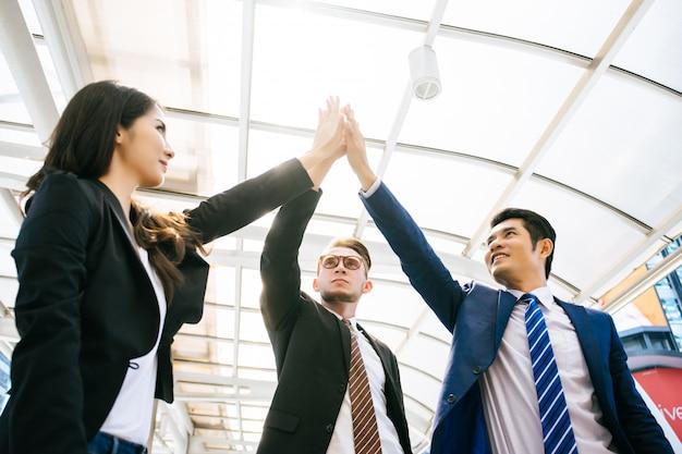 成功したビジネスチームは、オフィスの前で立っている間にハイレベル5を与え、笑顔を浮かべています。