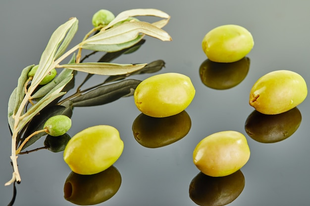 灰色の背景の上に横たわる果物とオリーブの木の枝を持つ5つのオリーブ