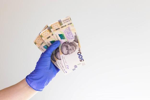Рука доктора в голубой перчатке держа украинские деньги. 5 сотен банкнот.