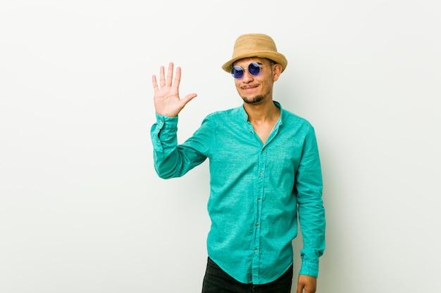 陽気な笑みを浮かべて指で番号5を示す夏服を着ているヒスパニック青年。
