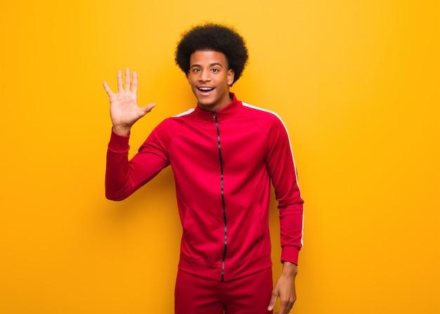 番号5を示すオレンジ色の壁の上の若いスポーツ黒人男性