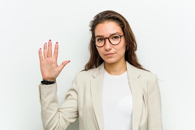 番号5の指で陽気な笑みを浮かべて若いヨーロッパの女性。