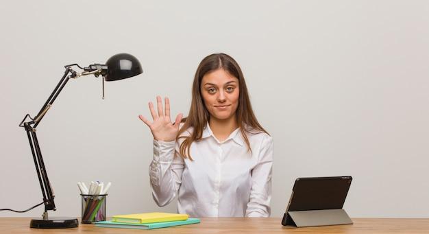 番号5を示す彼女の机で働く若い学生女性