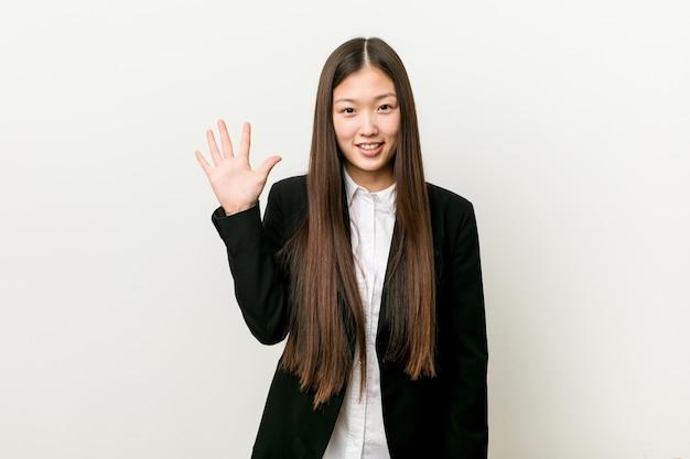 若いかなり中国のビジネス女性の指で陽気な表示数5を笑っています。