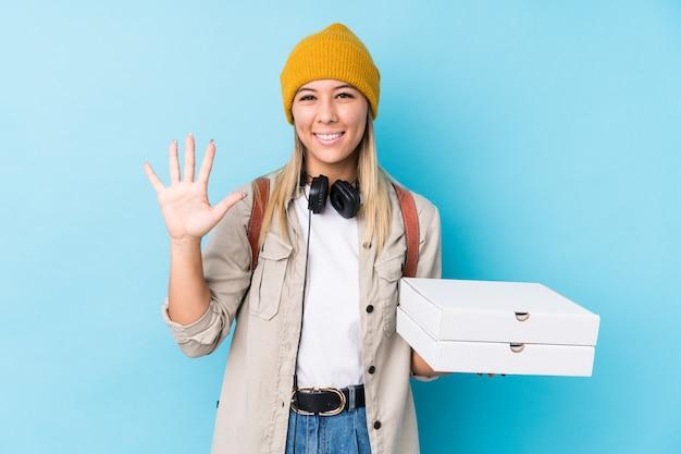 陽気な笑顔で示す番号5のピザを保持している若い女性の指