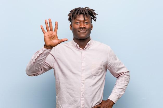 若いビジネスアフリカ黒人男性の笑みを浮かべて陽気な表示番号5を指で。