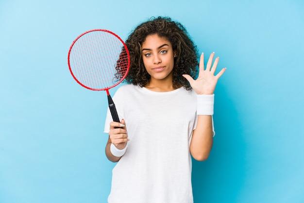 陽気な笑みを浮かべてバドミントンを演奏若いアフリカ系アメリカ人女性の指で5番を表示します。