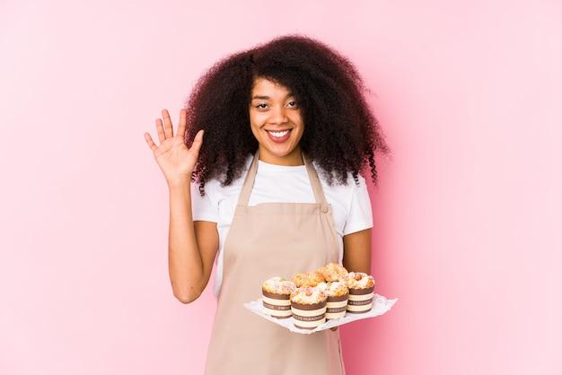 カップケーキを保持している若いアフロのペストリーメーカー女性分離された若いアフロのパン屋の女性が指で陽気な表示数5を笑顔します。