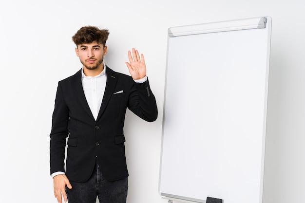 若いビジネスのコーチング男の指で陽気な表示数5を笑顔