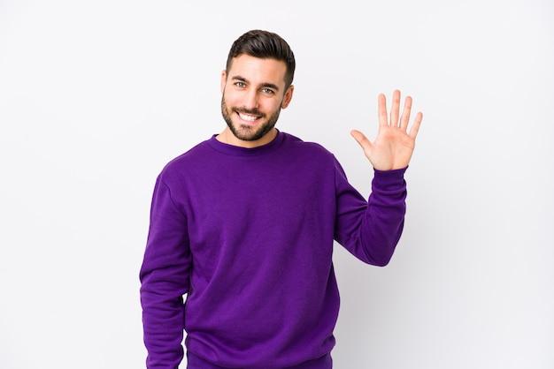 Молодой кавказский человек против белой стены усмехаясь жизнерадостный показ 5 с пальцами.