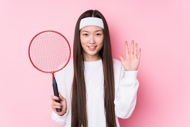 Молодая китайская женщина играя показ 5 бадминтона жизнерадостный с пальцами.