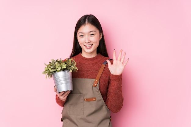 Молодая китайская женщина садовника держа показ завода 5 жизнерадостный показывая с пальцами.
