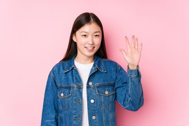 Молодая китайская женщина представляя в показе 5 розовой стены усмехаясь жизнерадостном с пальцами.