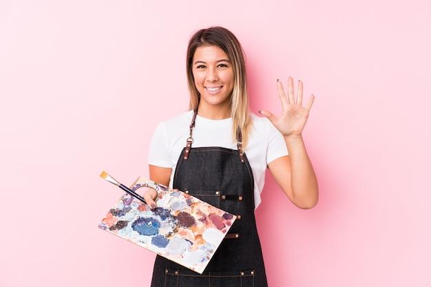 Женщина молодого художника кавказская держа номер 5 палитры усмехаясь жизнерадостный с пальцами.