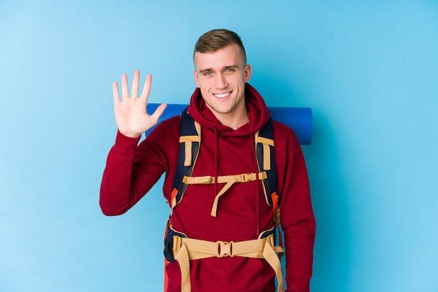 陽気な笑みを浮かべて指で5番を示す若い旅行者男
