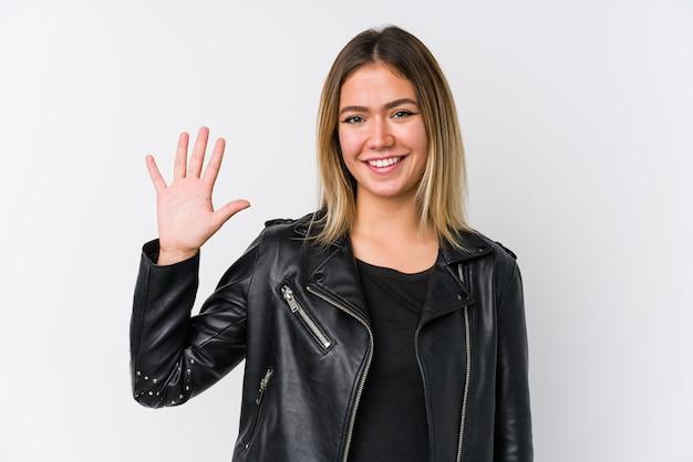 Молодая кавказская женщина нося показ черной кожаной куртки жизнерадостный 5 с пальцами.