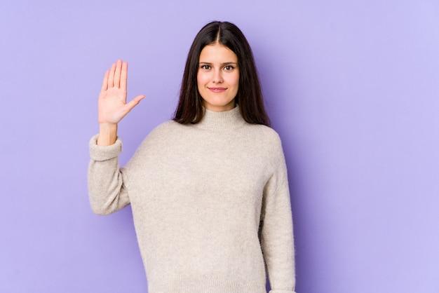 Молодая кавказская женщина изолированная на фиолетовой стене усмехаясь жизнерадостный показ 5 с пальцами.