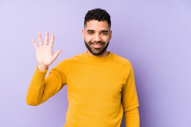 Человек молодой смешанной гонки арабский изолировал усмехаясь жизнерадостный показ 5 с пальцами.