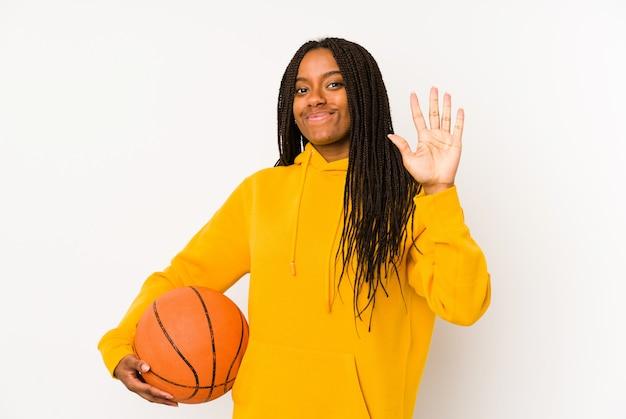 Молодая афро-американская женщина играя баскетбол изолировала усмехаясь жизнерадостный показ 5 с пальцами.