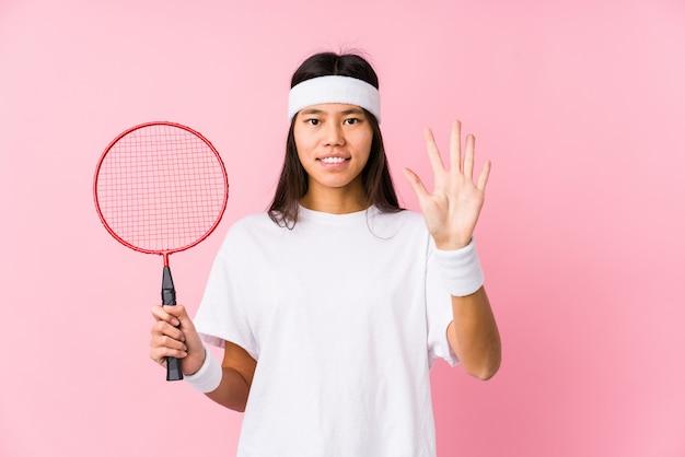 Молодая китайская женщина играя бадминтон в показе 5 розовой стены усмехаясь жизнерадостном с пальцами.