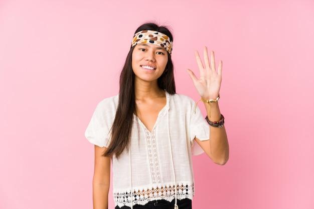 Показ 5 молодого китайского хиппи усмехаясь жизнерадостный с пальцами.