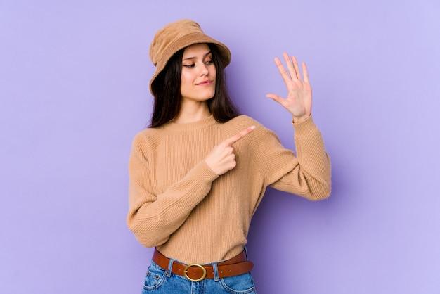 Молодая кавказская женщина на фиолетовой стене усмехаясь жизнерадостный показ 5 с пальцами.