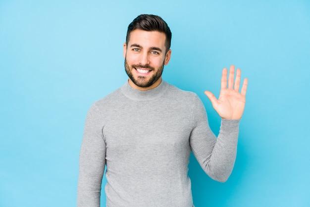 Молодой кавказский человек против сини изолировал усмехаясь жизнерадостный показ 5 с пальцами.