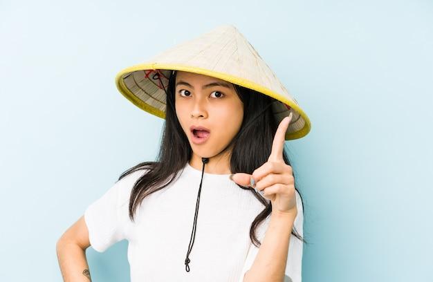 Молодая китайская женщина нося показ 5 вьетнамского сена усмехаясь жизнерадостный с пальцами.