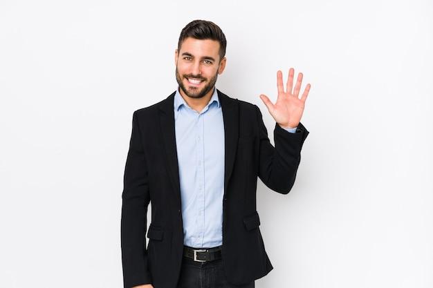 Молодой кавказский бизнесмен против белой стены усмехаясь жизнерадостный показ 5 с пальцами.