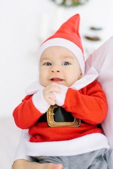 サンタクロースのスーツを着た生後5ヶ月の小さな子供が両親の手に横たわっている