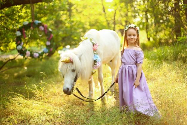 紫色のドレスを着た5歳のブロンドの女の子が白いポニーと立っています。