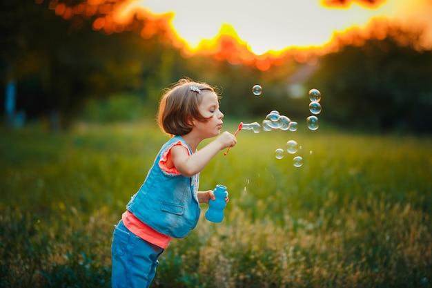 夕暮れ時屋外シャボン玉を吹く5歳の白人の子供女の子。