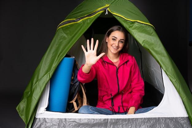 Молодая кавказская женщина внутри располагаясь лагерем зеленой палатки подсчитывая 5 с пальцами