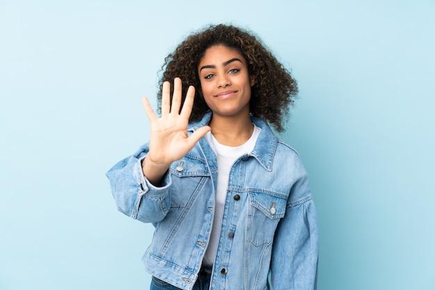 Молодая афро-американская женщина изолированная на голубом космосе подсчитывая 5 с пальцами
