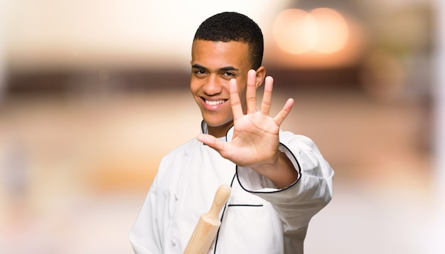 やり場のない壁に指で5を数える若いアフロアメリカンシェフ男