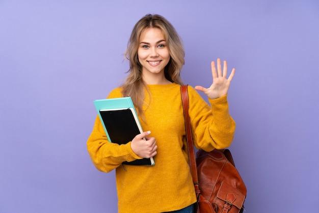 Девушка студента подростка на фиолетовой стене считая 5 с пальцами
