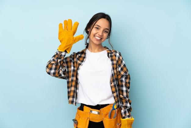 Молодая женщина электрика изолированная на голубой стене подсчитывая 5 с пальцами