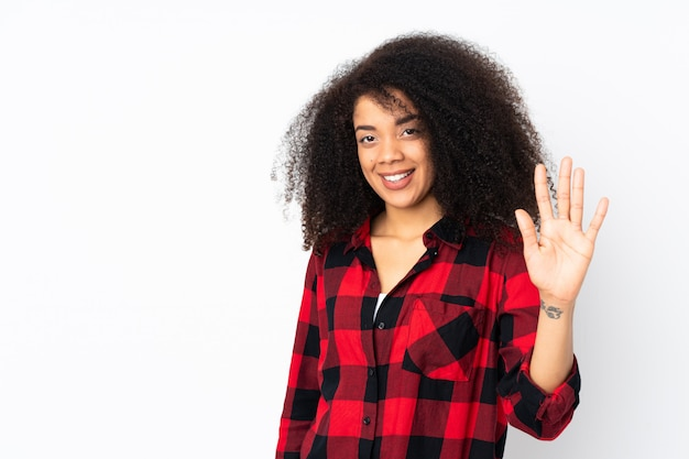 Молодая афро-американская женщина над стеной подсчитывая 5 с пальцами