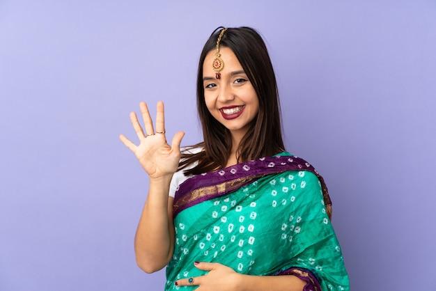 Молодая индийская женщина изолированная на фиолетовой стене подсчитывая 5 с пальцами